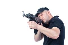 Homem que aponta a metralhadora de AK-47 Foco na arma Fotografia de Stock