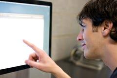 Homem que aponta no ecrã de computador Imagens de Stock