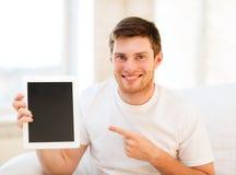 Homem que aponta no PC da tabuleta em casa Foto de Stock Royalty Free