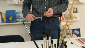 Homem que aponta o lápis com uma faca grande Imagens de Stock