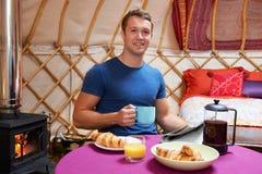 Homem que aprecia o café da manhã enquanto acampando em Yurt tradicional Imagem de Stock