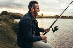 Homem que aprecia a pesca perto de um lago fotos de stock royalty free