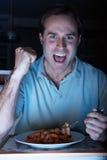 Homem que aprecia a refeição enquanto prestando atenção à tevê Foto de Stock Royalty Free