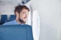 Homem que aprecia sua viagem pelo avião foto de stock