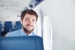 Homem que aprecia sua viagem pelo avião imagem de stock royalty free