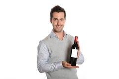 Homem que apresenta uma boa garrafa de vinho Fotos de Stock