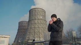 Homem que aquece as mãos na área industrial vídeos de arquivo