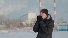Homem que aquece as mãos perto da fábrica vídeos de arquivo