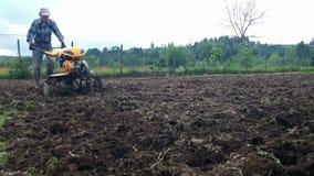 Homem que ara o campo usando um cultivador, preparação do jardim filme