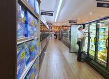 Homem que armazena refrigeradores em um supermercado imagem de stock