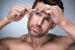 Homem que arranca as sobrancelhas com pinça imagens de stock