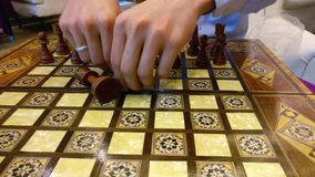 Homem que arranja partes de xadrez em uma placa de madeira que prepara-se para jogar vídeos de arquivo