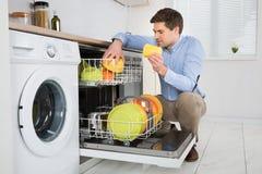 Homem que arranja pratos na máquina de lavar louça Foto de Stock Royalty Free