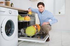 Homem que arranja pratos na máquina de lavar louça fotografia de stock royalty free