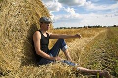 Homem que assenta perto da esfera e do descanso do centeio Fotografia de Stock Royalty Free