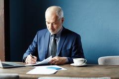 Homem que assina um contrato foto de stock royalty free