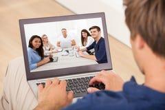 Homem que assiste à reunião da conferência sobre o portátil em casa Imagens de Stock Royalty Free