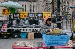 Homem que atravessa cartazes em um vendedor ambulante em Manhattan, perto da entrada à ponte de Brooklyn foto de stock
