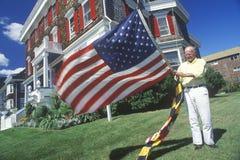 Homem que aumenta o americano e as bandeiras de Maryland, Cape May, New-jersey Fotografia de Stock Royalty Free