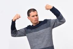 Homem que aumenta seus braços que fazem os bíceps e o sinal da vitória e da força foto de stock royalty free