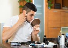 Homem que barbeia a cara com ajustador fotografia de stock