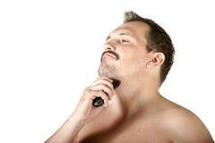 Homem que barbeia a cara com lâmina elétrica Fotografia de Stock Royalty Free