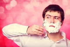 Homem que barbeia no fundo vermelho Imagens de Stock Royalty Free