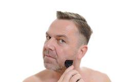 Homem que barbeia sua barba com uma lâmina Fotos de Stock