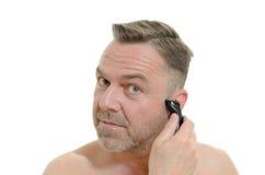 Homem que barbeia sua barba com uma lâmina Fotografia de Stock Royalty Free