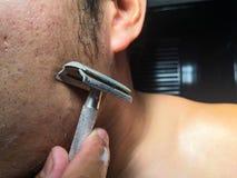 Homem que barbeia sua barba no banheiro foto de stock royalty free