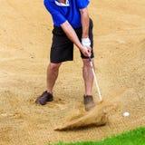 Homem que bate a bola de golfe fora de um depósito imagens de stock