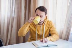 Homem que bebe o café quente e a leitura Foto de Stock