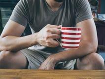 Homem que bebe o chá ou o cacau quente do café Imagem de Stock