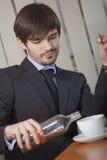 Homem que bebe pelo trabalho de escritório Imagem de Stock