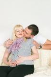Homem que beija a esposa grávida Fotografia de Stock Royalty Free