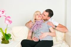 Homem que beija a esposa grávida Imagem de Stock