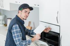 Homem que cabe o fogão novo na cozinha fotos de stock royalty free