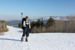 Homem que caminha na neve entre montanhas Foto de Stock