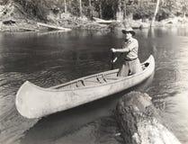 Homem que canoeing abaixo do rio Fotografia de Stock