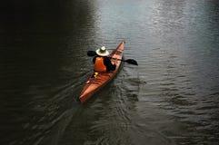 Homem que canoing no lago Imagens de Stock