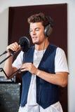 Homem que canta ao guardar o microfone no estúdio Imagens de Stock