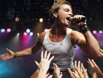 Homem que canta perto dos fãs adoradores Imagem de Stock Royalty Free