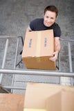 Homem que carreg uma caixa fotografia de stock