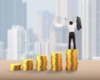 Homem que cheering sobre pilhas douradas das moedas foto de stock royalty free