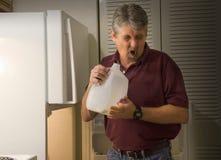 Homem que cheira o leite ácido podre estragado Imagens de Stock
