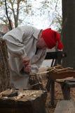 Homem que cinzela uma vestidura histórica da colher de madeira Imagem de Stock