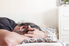 Homem que cobre sua cara no sofrimento Fotografia de Stock