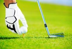 Homem que coloc a esfera de golfe no T Fotografia de Stock