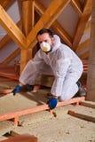 Homem que coloca a camada da isolação térmica na construção Foto de Stock Royalty Free