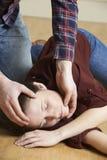 Homem que coloca a mulher na posição da recuperação após o acidente Imagens de Stock